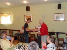 FIDE Open Pohorela 2010-- Ivan Kraml odovzdáva cenu pre najlepšieho doR 1800Júlia Bellu zPodbrezovej    Od1.8. - 7.8.2010 sa konal šachový turnaj už 10.ročník šachového turnaja Fide Open Pohorelá.   Oproti predošlým ročníkom turnaj bol vtrvaní sede